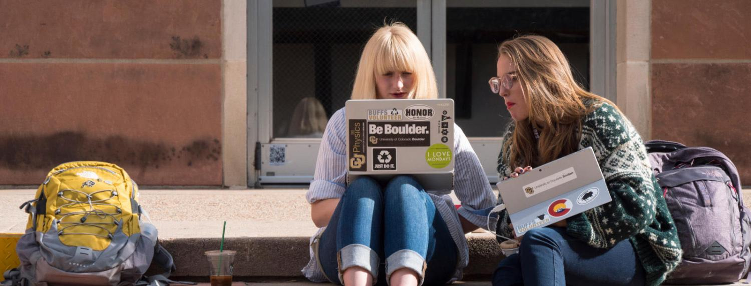 Two female students looking at a laptop while sitting outside of Norlin Library