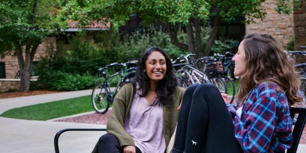 Two female students sitting on a bench on campus talking