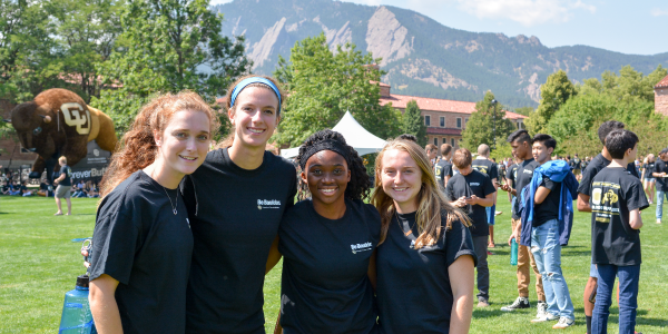 Students posing on campus with mountains in the background