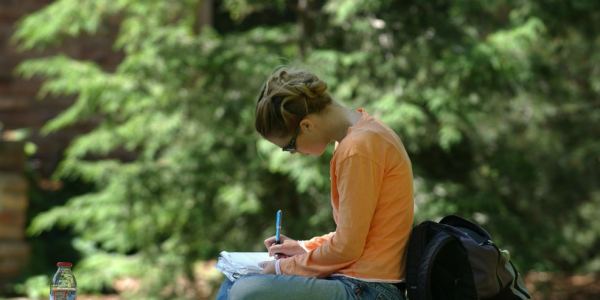 Student Sitting on Wall, Writing