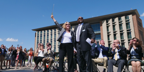 Drones lift a 'Cut Before Flight' ribbon to Ann Smead (left) and Brian Argrow at the Aerospace Engineering Sciences Building grand opening ceremony on August 26, 2019.