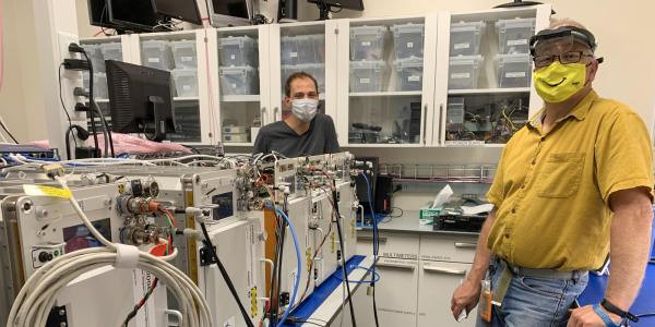 Tobias Niederwieser and Alexander Hoehn in a BioServe laboratory with five FRDIGE units slated for delivery to NASA and the International Space Station.