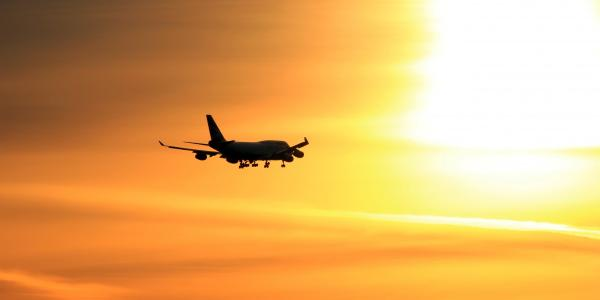 Plane flying toward a sunset.