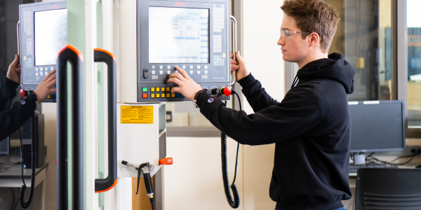 A student working in the Machine Shop with a CNC machine.