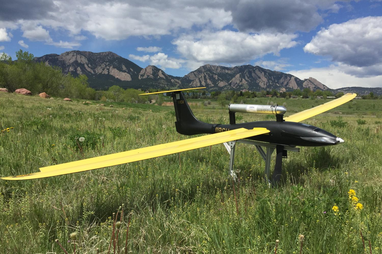Unmanned aerial vehicle resting on the ground with the flatirons in the background.