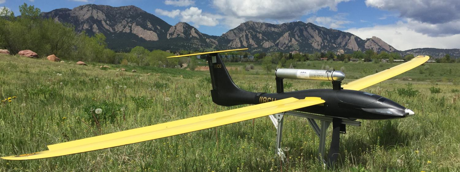A UAV resting on the ground with the flatirons in the background.