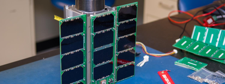 A CubeSat on a workbench.