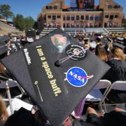 "A graduation cap with an ""I am a space buff"" bumper sticker and NASA logo."