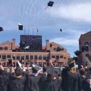 2018 graduates toss their caps.