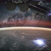 An image taken from the International Space Station shows orange swaths of airglow hovering in Earth's atmosphere. NASA's new Atmospheric Waves Experiment will observe this airglow from a perch on the space station to help scientists understand, and ultimately improve forecasts of, space weather changes in the upper atmosphere.