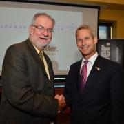 Dean Rob Davis and Lockheed Martin CTO Keoki Jackson shake hands