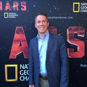 Bobby Braun in front of a National Geographic sign saying 'Mars'.
