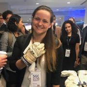 Shayna Hume tries on a spacesuit glove that had previously flown to space.