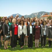 The Women in Aerospace Symposium attendees standing for a photo outside with the Flatirons in the background.