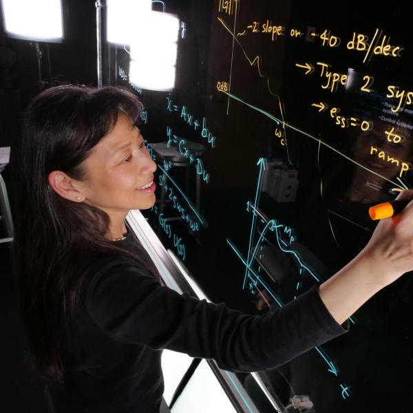 Faculty writing on light board