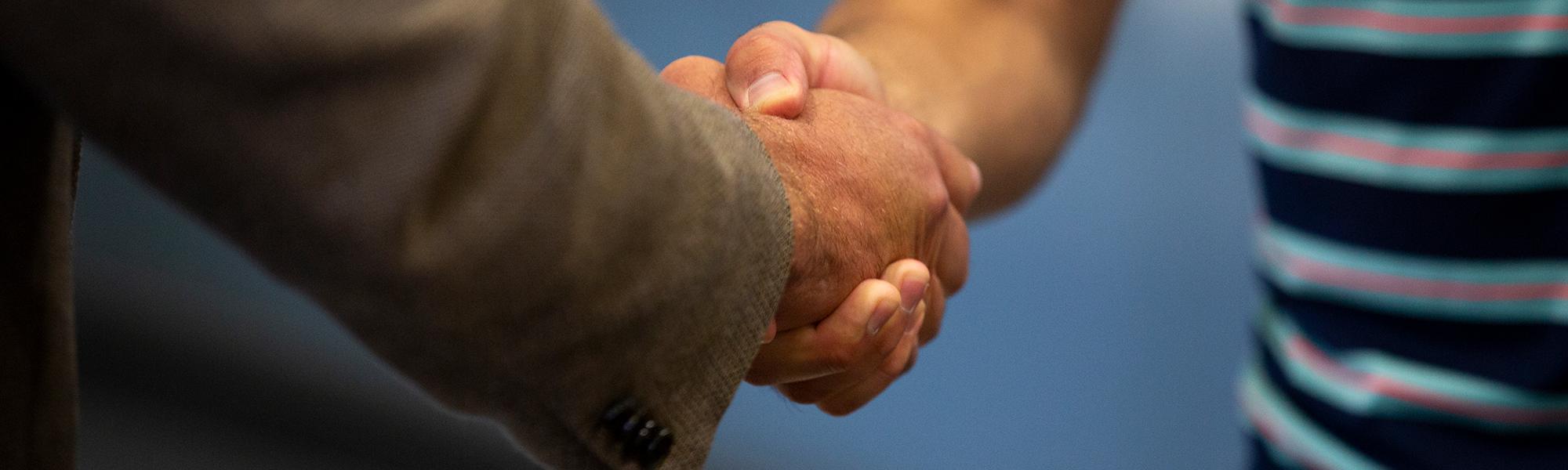 CU Boulder alumni shaking hands