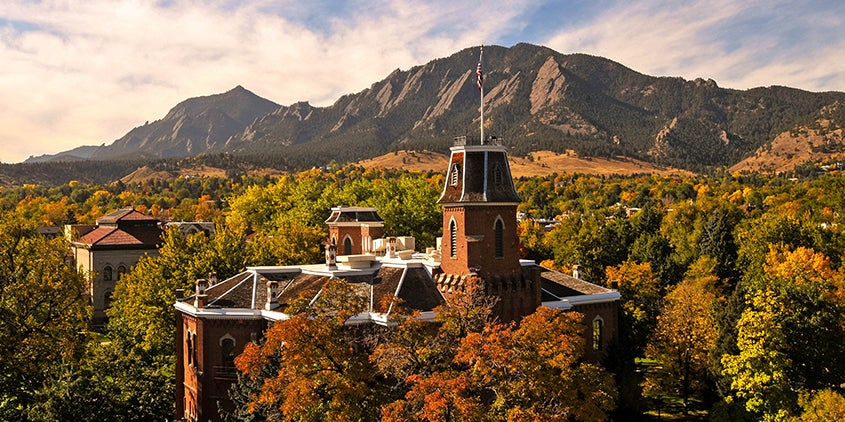 old main building on cu boulder campus during fall