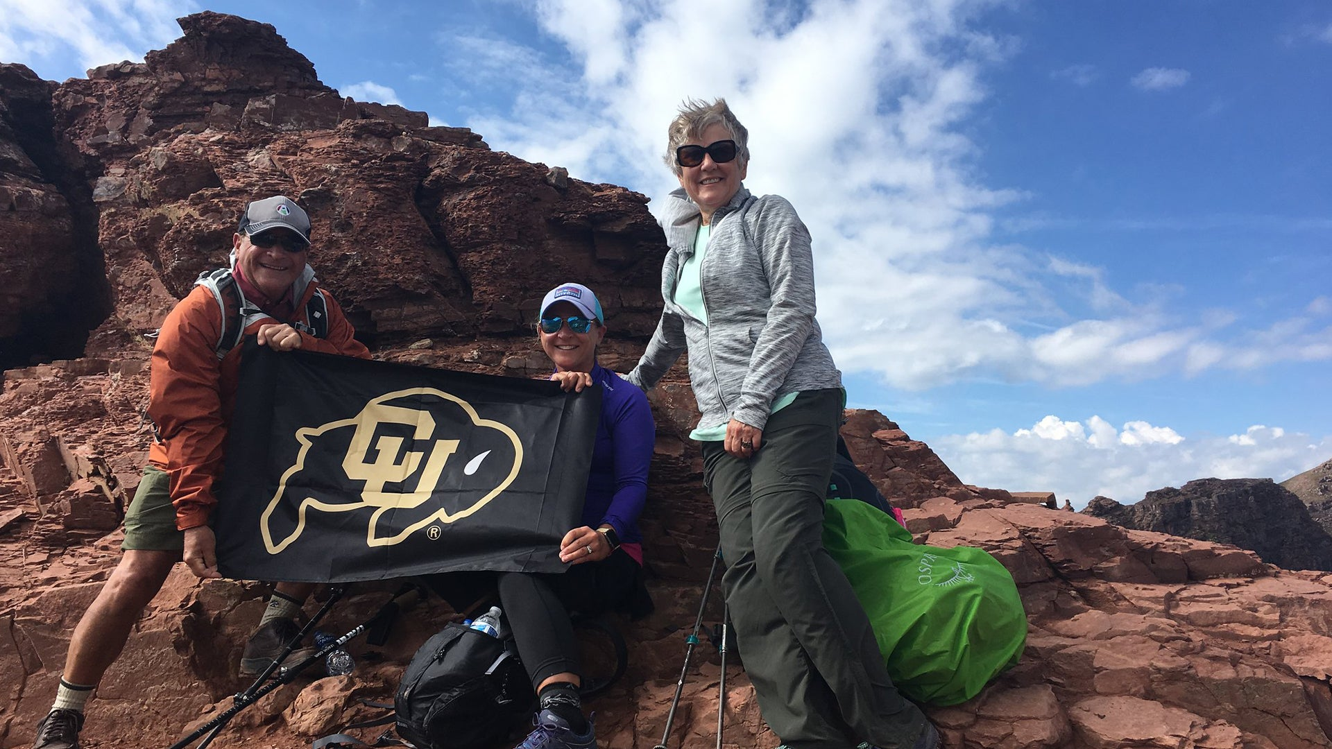 A group of alumni with a CU Bouder flag on a mountaintop