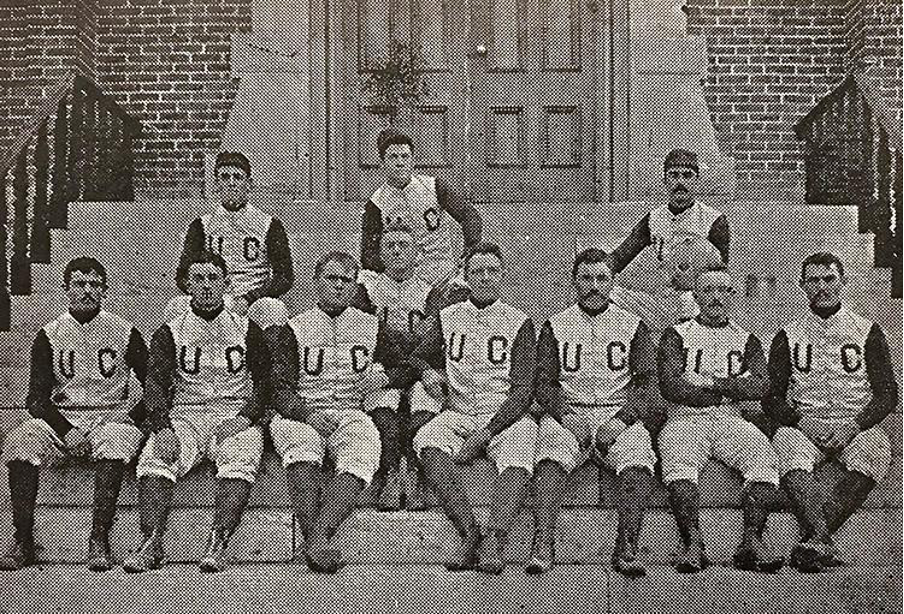 Part of CU's first football team sitting on the steps in front of Old Main