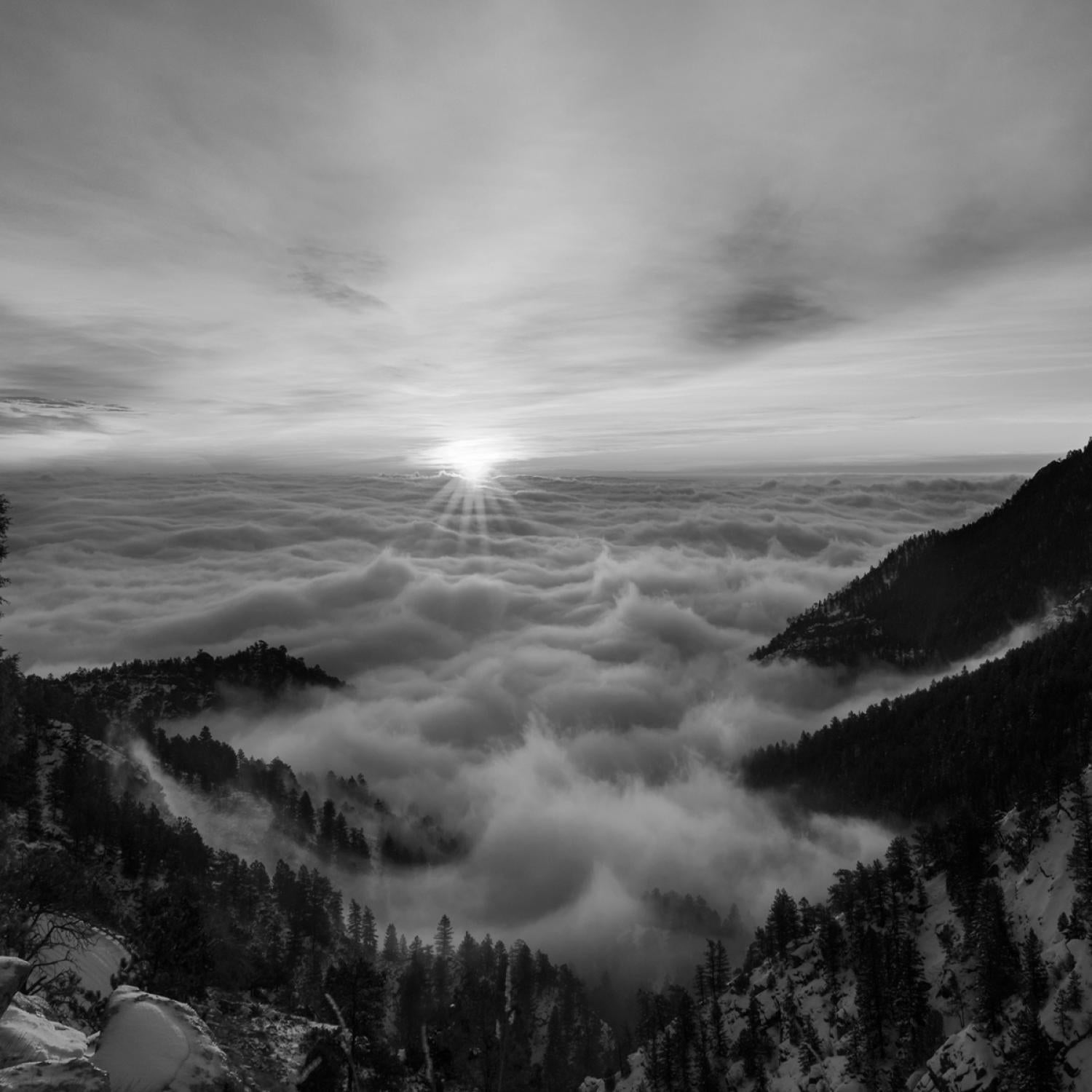 black and white photo of sunrise between peaks