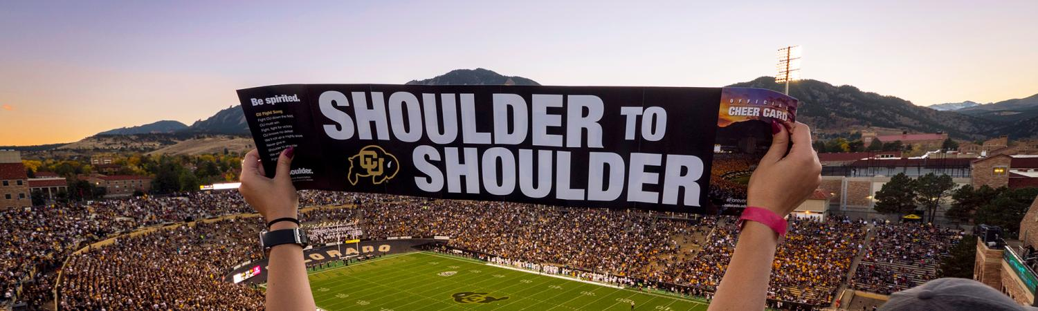 """Student holding up a sign that reads """"Shoulder to Shoulder"""" in Folsom Field"""