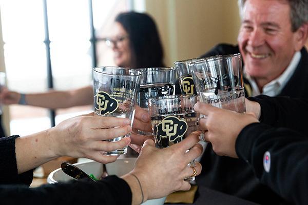 CU Boulder alumni clink pint glasses