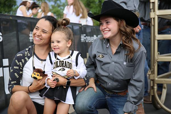 young family and CU Boulder fans pose with one of Ralphie's handlers
