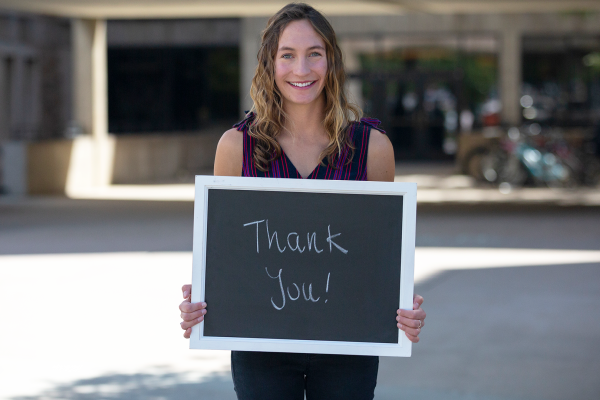 "student holding chalkboard saying ""thank you"""