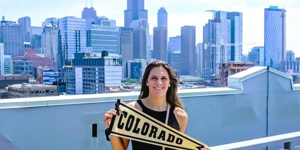 alumni holding Colorado pennant in front of skyline