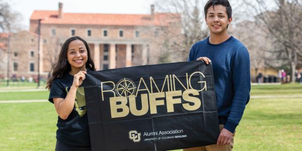Alumni holding CU Boulder flag