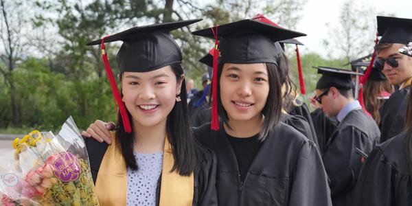 two recent cu boulder graduates in cap, gown and graduation regalia at commencement