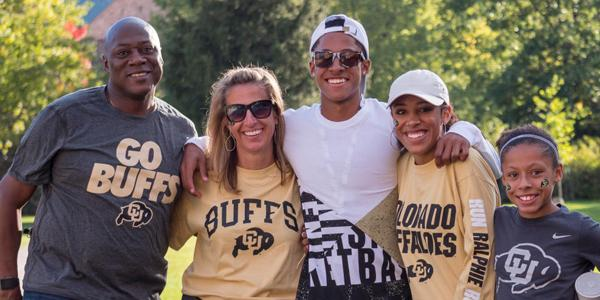 """A family of five wearing """"go buffs"""" tshirts stand with their arms around each other"""