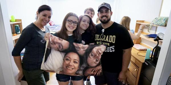 A family poses with their student in a dorm room while holding a keepsake pillowcase