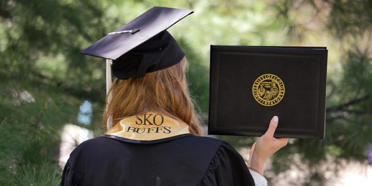 CU Boulder graduate in commencement regalia