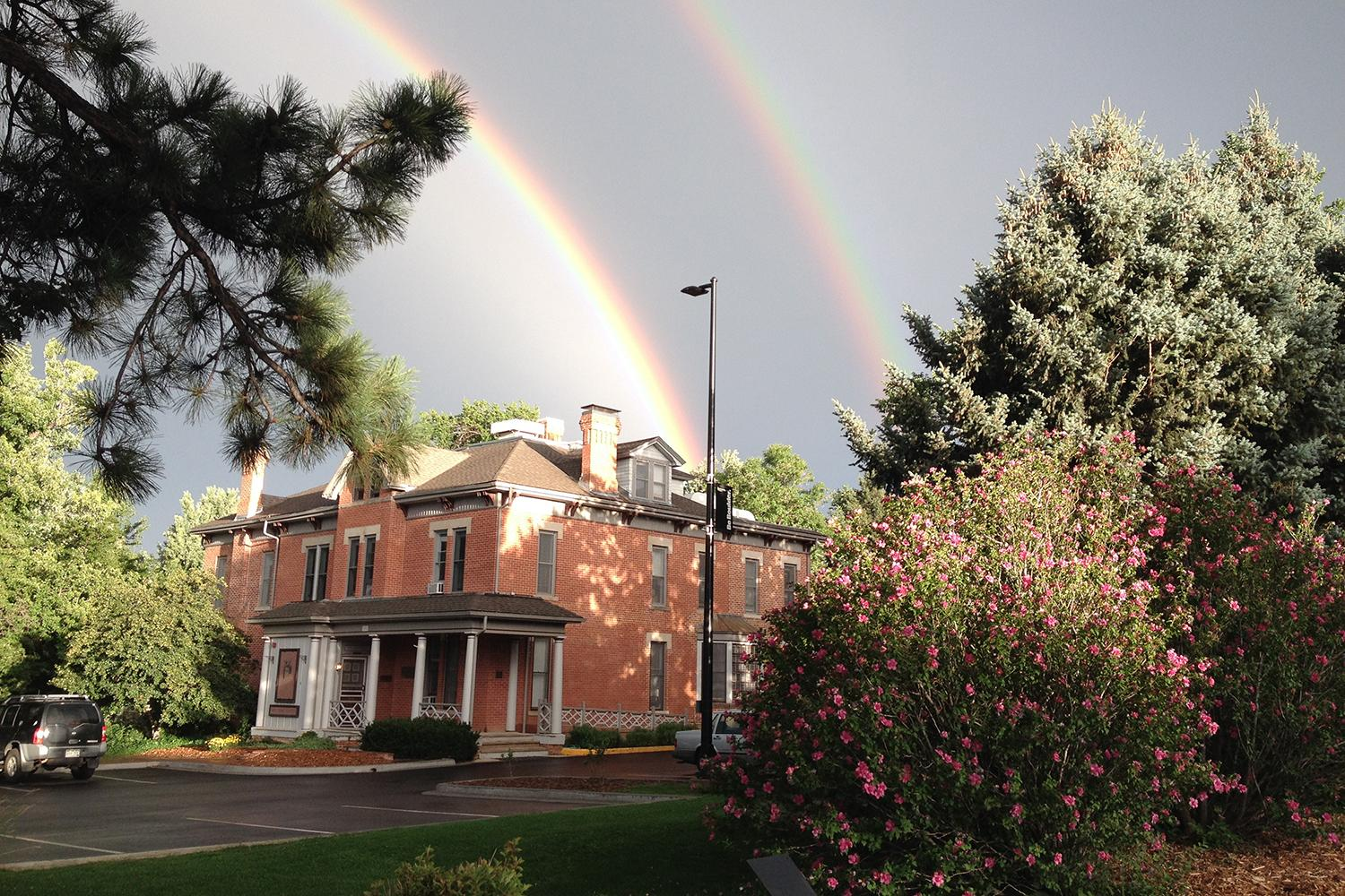 cu boulder Koenig alumni center under a double rainbow