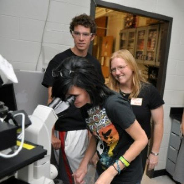 Dan and Kristi showing a high school student cells