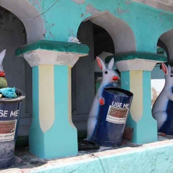 Nightmarish rabbit statues holding garbage bins