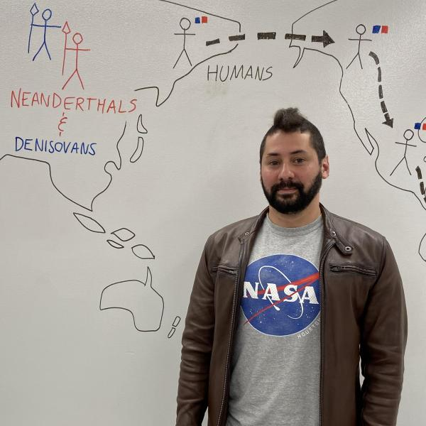 Fernando wearing a NASA shirt standing in front of a white board