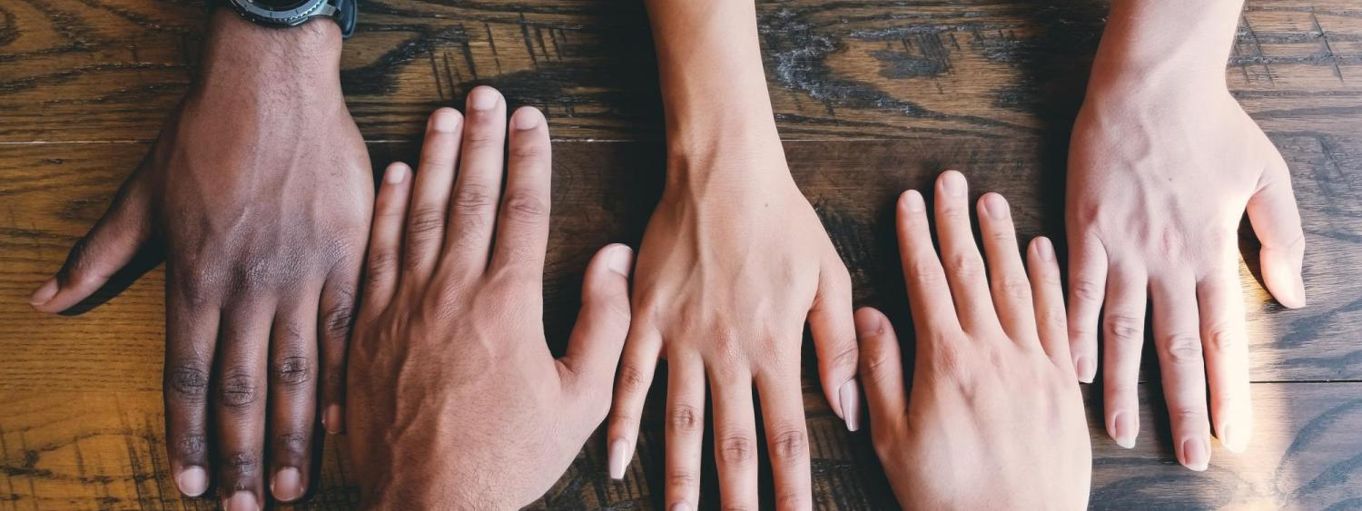 5 human hands on a wooden table
