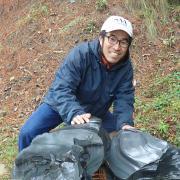 Akira Ichikawa in the field with big black rocks