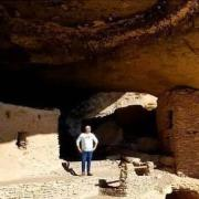 Carlton standing in a cliff dwelling