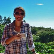 Emily Hite standing on a deck holding a cup of coffee