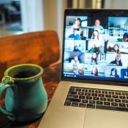 Laptop open to a Zoom meeting with a cup of coffee on the side