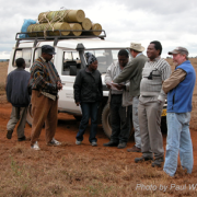 Terry with locals in the field  in Africa by a Jeep