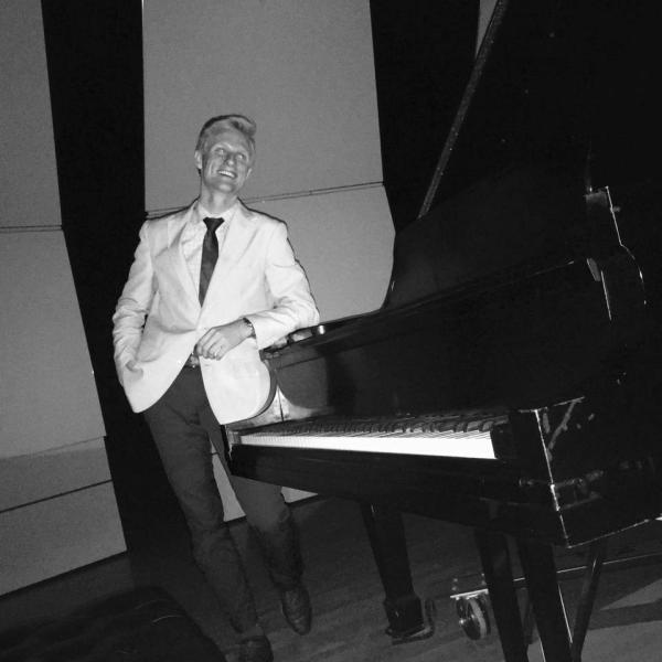 Kirk Long next to a piano