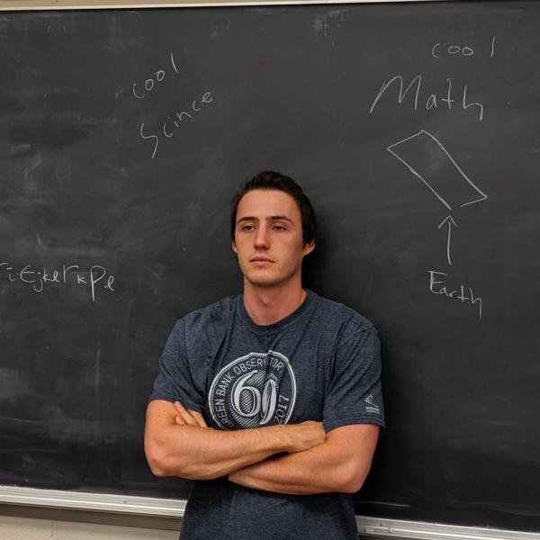 Parker Hinton in front of a blackboard