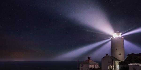 A lighthouse burning through night-time fog