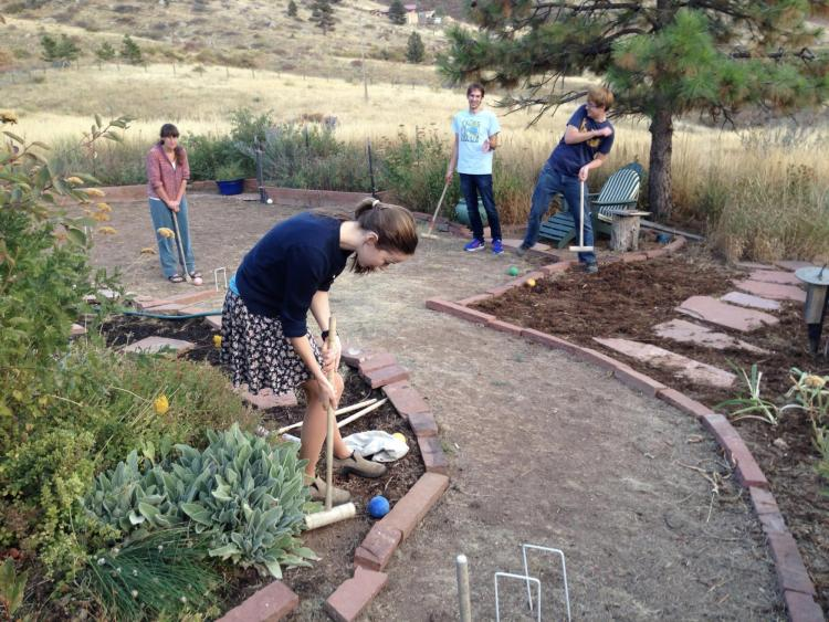 Faculty members playing croquet