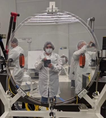 Amanda White working on a mirror in a clean room