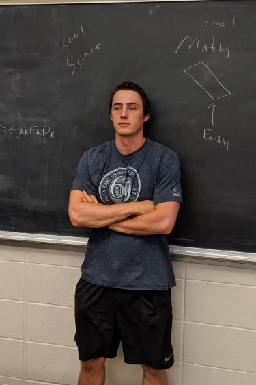 Parker Hinton in front of a blackboard